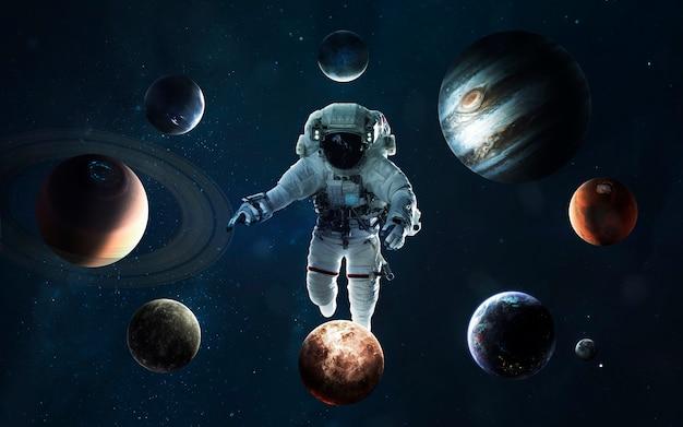 Астронавт в центре солнечной системы. символ освоения космоса. элементы этого изображения, предоставленные наса