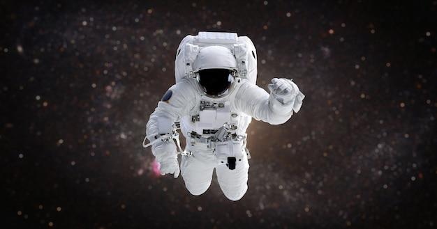Астронавт в открытом космосе на фоне галактики