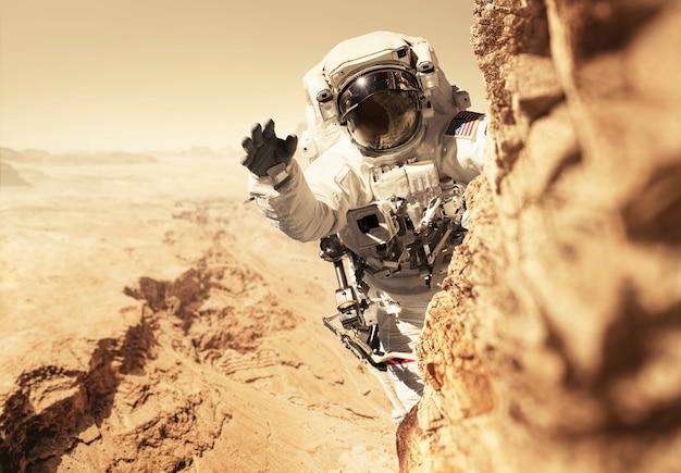 火星宇宙飛行士は赤い惑星への使命を帯びており、岩の上の山に登っています。宇宙人は新しい惑星火星を征服し、人口を増やします。惑星火星と人々、概念。新しい家へようこそ