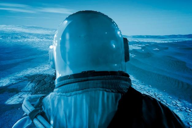 Астронавт на поверхности луны рядом с космической станцией б. элементы этого изображения предоставлены наса