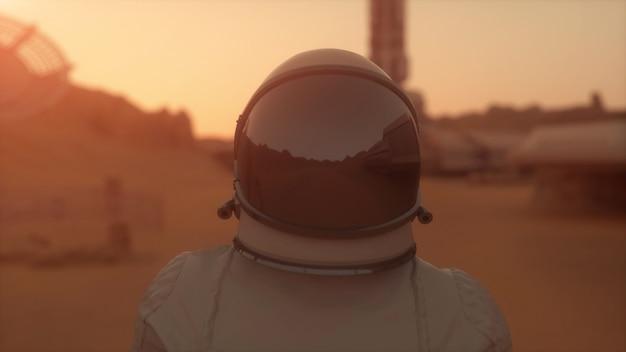 火星の宇宙飛行士。火星の表面を歩く宇宙飛行士。植民地化の概念。 3dレンダリング。
