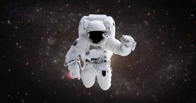 Astronaut in the open space against the galaxy