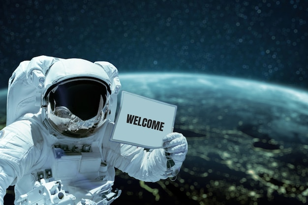 Astronaut in a space suit shows a card with the text welcome spacewalk against the background of the planet earth. spaceman in outer space