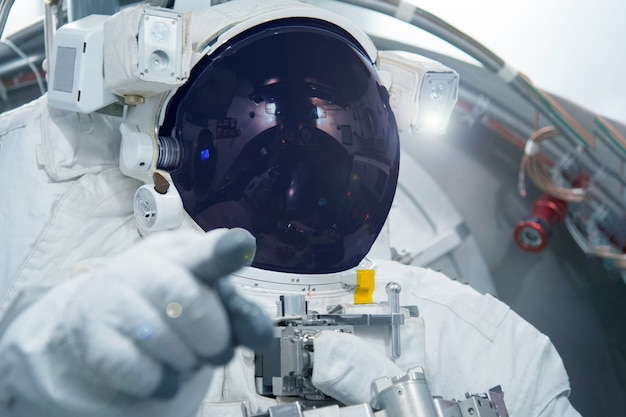 Astronaut in a spacesuit point finger forward elements of this image were furnished by nasa