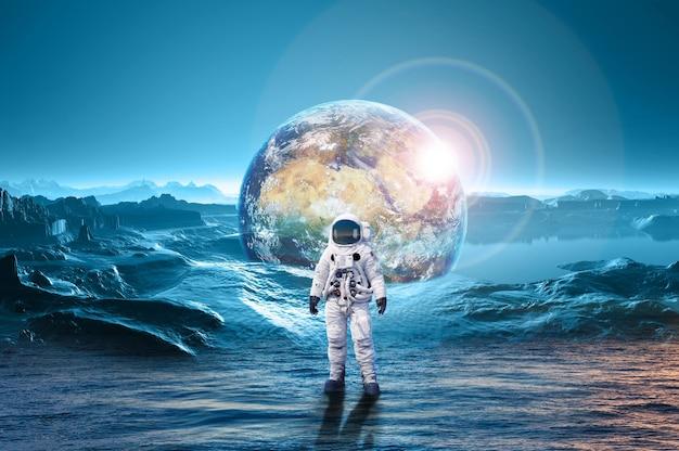 지구 행성 행성 지구와 바다 밖으로 서 있는 우주 비행사