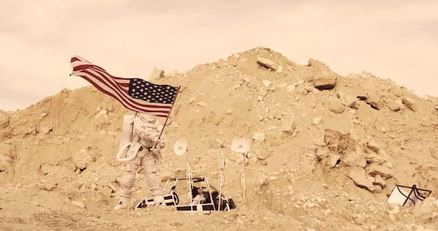 Astronaut with american flag standing on the rocky mountain of the alien red planet/ mars. first manned mission on mars