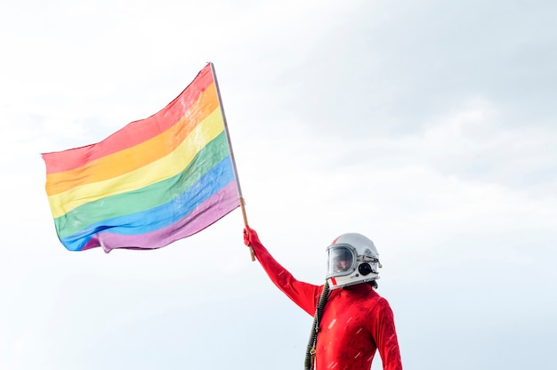 Astronaut with helmet holding a gay pride flag.concepto lgbt