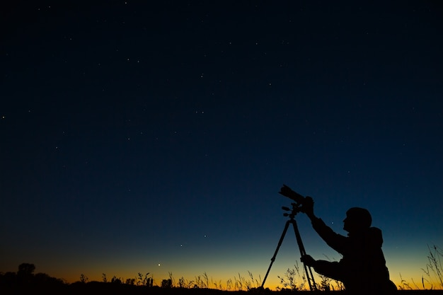 The astronomer photographs the night starry sky on a digital camera using a tripod