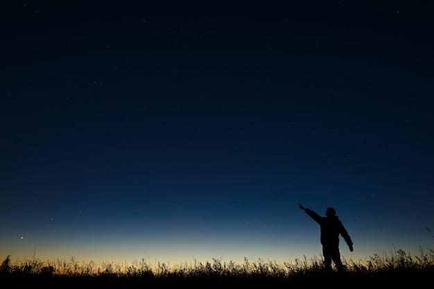 Астроном указывает рукой ночью на звездное небо на фоне сумеречного горизонта.