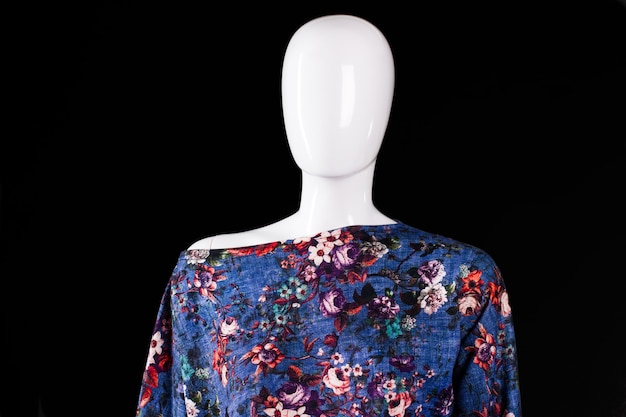 Asymmetric top with floral pattern. blue top on white mannequin. woman's fashionable summer top. trendy clothing made of cotton.