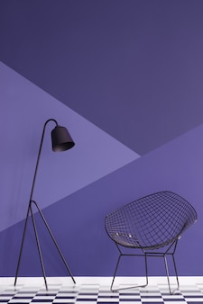 Asymmetrical violet wall in modern living room interior with metal lamp and black armchair on checkered floor. real photo