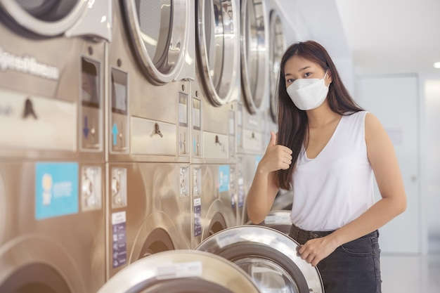 자동 세탁기가 많은 세탁소에서 마스크를 쓴 미녀가 빨래를 하고 있다.
