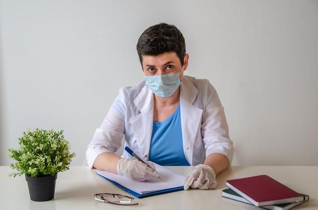 医師の予約時。保護マスクを着用した真面目な女性セラピストが診断を書き留め、オフィスの患者の反対側の机に座っている