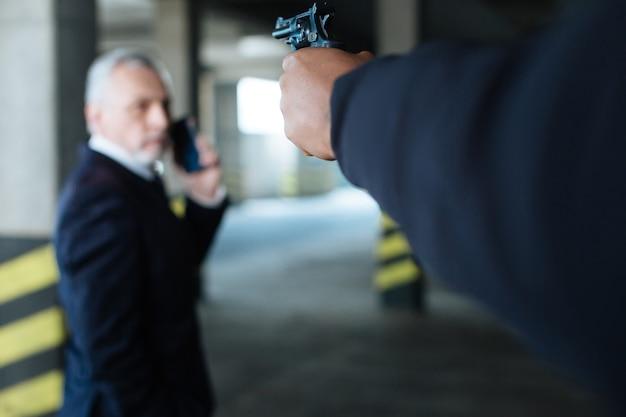 총구에서. 위험한 강화 범죄자의 손에있는 동안 사업가를 향한 권총의 선택적 초점