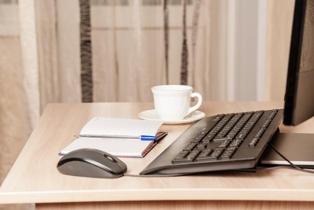 Дома клавиатура лежит на белом деревянном столе. блокнот, чашка кофе и мышь.
