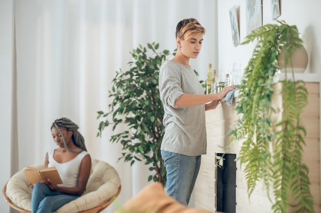 自宅で。部屋を掃除している金髪の女の子、椅子に座っている彼女のガールフレンド