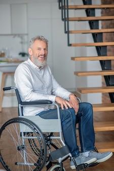 집에서. 집에서 흰 셔츠와 청바지를 입은 장애인 회색 머리 남자