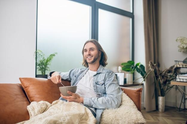 家に。自宅で休んでいるジーンズシャツの長髪の男