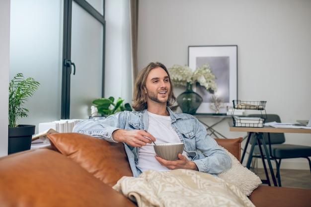 家に。自宅で時間を過ごすジーンズシャツの長髪の男