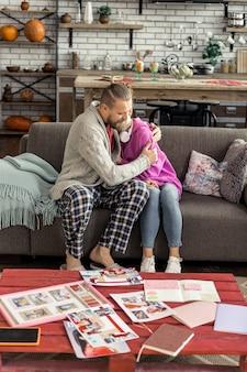 집에서. 집에서 거실에서 소파에 앉아 잘 생긴 아버지와 딸 사랑