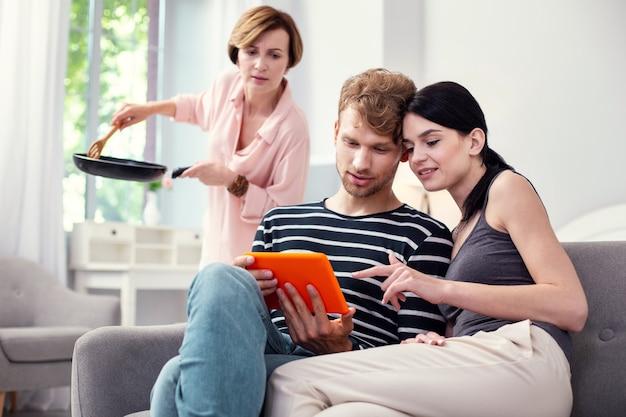 自宅で。タブレット画面を見ながら一緒に座っている素敵な楽しいカップル