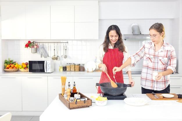 Дома два приятеля развлекаются на кухне. сестры вместе готовят спагетти на кухне. на кухне две подруги