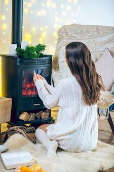 家に。暖炉のそばに座っている白い服とストッキングの若い女性