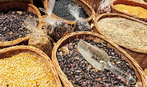 На рыночных прилавках фасоль, чечевица, горох, нут. веганские белки. рынок органических здоровых свежих продуктов. зеленая трава размыта на фоне. растительный рацион.