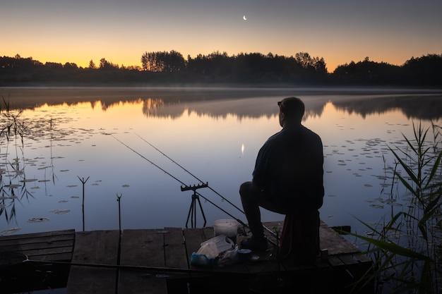 Ночью на пристани сидит рыбак с удочками для рыбалки на озере.