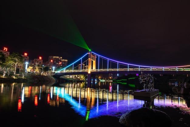 夜、小川は橋の色とりどりの光を反射します