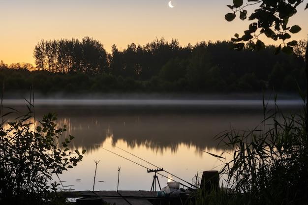 Ночью на причале устанавливают две удочки для рыбалки на озере.