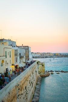В разгар туристического сезона толпа туристов гуляет на закате по дороге из новой части города отранто в старую.
