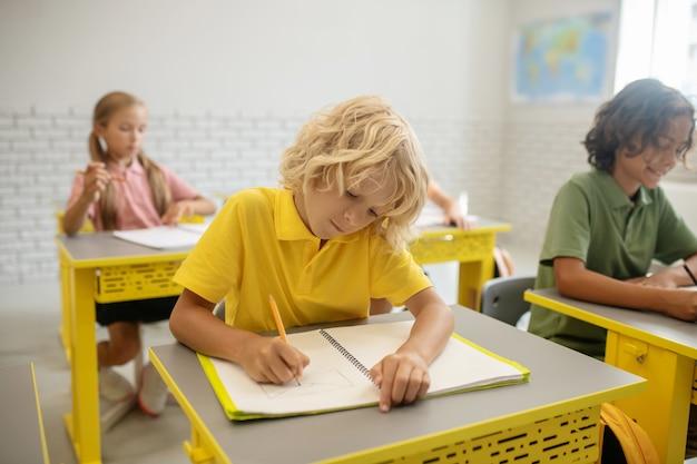学校で。教室の机に座っている子供たち