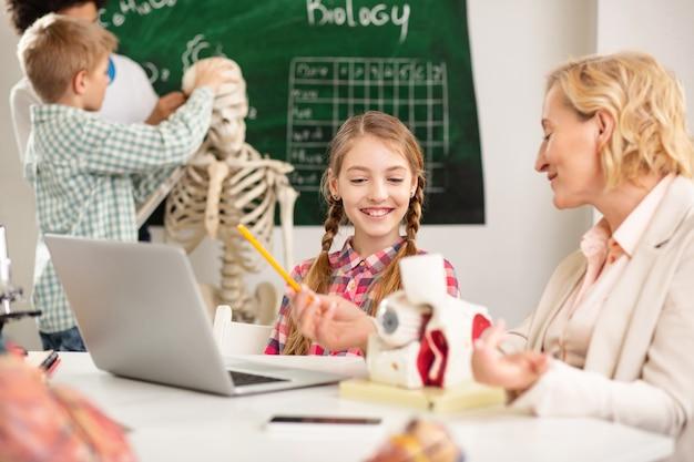 학교에서. 그녀의 선생님과 이야기하는 동안 테이블에 앉아 기쁘게 즐거운 소녀