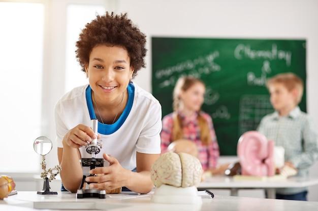 В школе. позитивный умный мальчик на уроке биологии во время учебы в школе