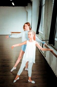 バレエのレッスンで。赤毛のバレエ教師とバレエのレッスンをしながら真剣に見える彼女の生徒たち