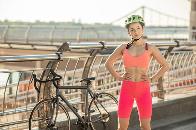 橋で。橋に立っている明るいスポーツウェアの若いサイクリスト