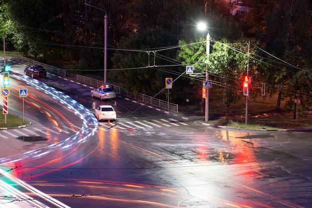 밤에 교차로에서 운전자가 보행자를 폭행하고 넘어뜨렸습니다. 경찰은 도로 교통 사고를 작성합니다. 비상 깜박이는 표시등이 있는 경찰 경감차.