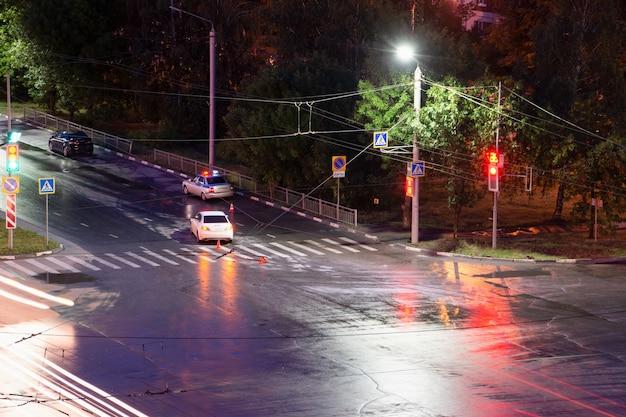 밤에 교차로에서 운전자가 보행자를 폭행하고 넘어뜨렸습니다. 경찰은 도로 교통 사고를 작성합니다. 교통 위반. 비상 깜박이는 표시등이 있는 경찰 경감차.