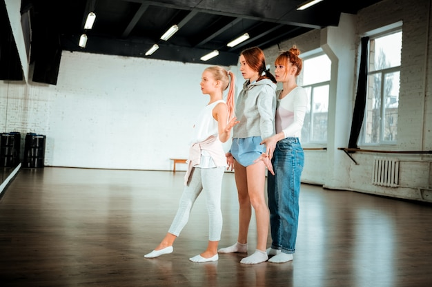 ダンスレッスンで。スタジオで生徒と一緒に働いている間真剣に見える赤毛の若いダンス教師