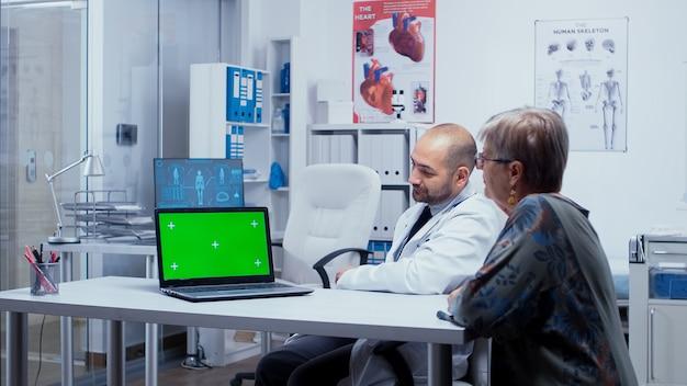 의사 사무실에서 은퇴한 노인 환자에게 녹색 화면으로 설명하고 있습니다. 앱 또는 광고에 대한 크로마 키 키잉을 제거할 준비가 된 모형 모형 격리 배경