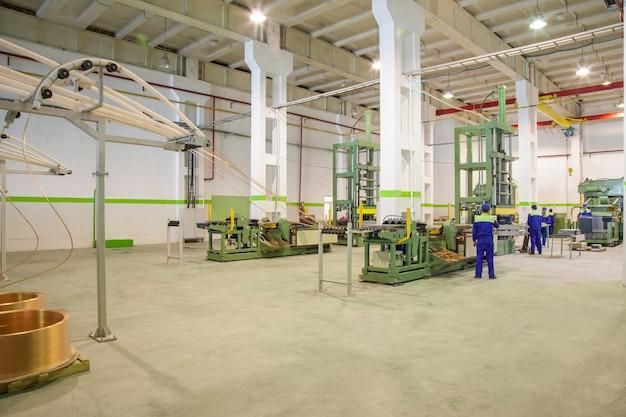 ロールからの銅管の展開と管理された切断のための工場設備で