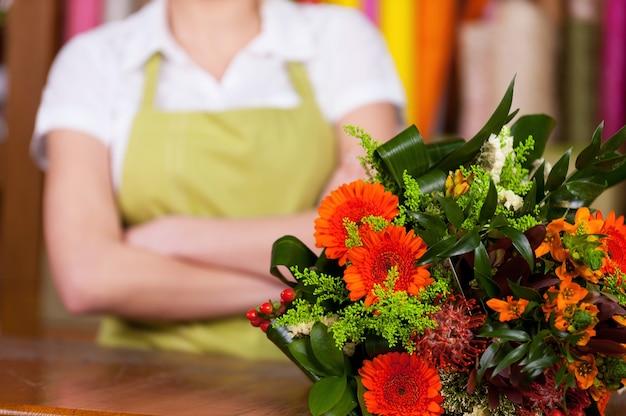 В цветочном магазине. обрезанное изображение молодой женщины со светлыми волосами в фартуке, держащей скрещенными руками, в то время как букет цветов кладет o передний план