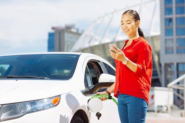 На заправке. умная молодая женщина с помощью своего мобильного телефона на заправке