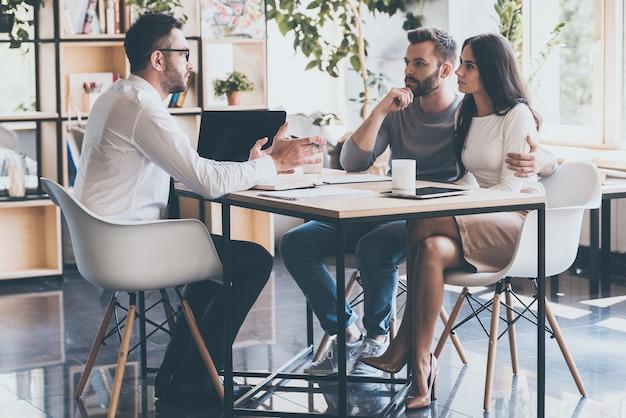 재무 고문과의 회의에서. 집중된 젊은 부부는 서로 결속을 다지고 책상에 앉아 재정 고문의 말을 듣습니다.