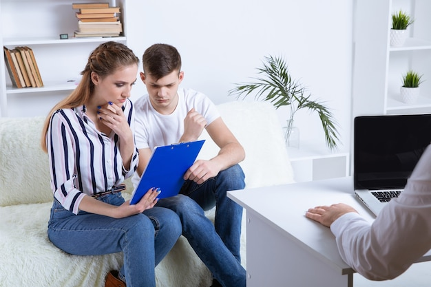 심리학자에서. 의사가 메모를 하는 동안 아름다운 젊은 부부가 소파에 앉아 포옹을 하고 있다