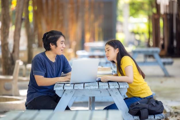 В общественном парке за столиком сидит счастливая молодая пара с ноутбуком.