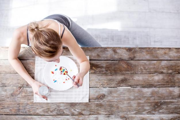 В таблице. вид сверху унылой молодой женщины, принимающей таблетки, сидя за столом