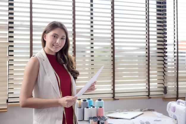 На работе делается портрет улыбающегося модельера и творческой женщины.