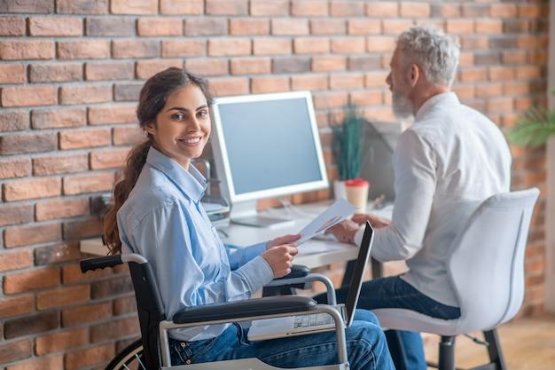 직장에서. 사무실에서 동료와 함께 일하는 장애인 젊은 여성